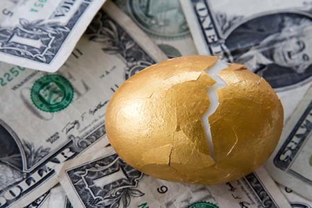 Golden egg with cracked shell on money